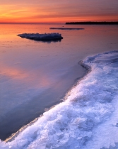 The sun rises over Lake Michigan on Newport Bay while ice forms on the shore and shallow limestone reefs just under the water, Newport Bay, Lake Michigan, Newport State Park, Door County, Wisconsin.
